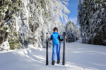 Full length portrait of smiling happy young female skier in winter forest. Woman is wearing blue ski suit helmet and orange glasses, holding skis. Winter sports concept. Carpathian Mountains, Bukovel