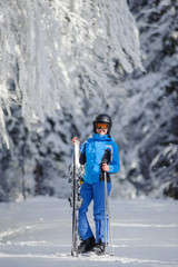 Portrait of young happy female skier standing enjoying sunny day against beautiful snow covered trees on the background. Woman is holding her skis in one hand and ski poles in another. Bukovel