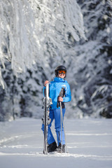 Isolated portrait of young happy female skier standing enjoying sunny day against beautiful snow covered trees on the background. Girl is holding her skis in one hand and poles in another. Bukovel