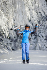Full length portrait of young happy female skier standing enjoying sunny day against beautiful snow covered trees on the background. Girl is holding her skis and ski poles up. Bukovel, Ukraine