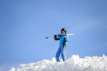 Portrait of young female skier standing on top of the mountain against blue sky on a sunny day. Woman is holding skis on her shoulder smiling and looking into the camera. Winter sports concept.