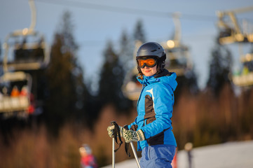 Close-up portrait of young female skier against ski-lift on a sunny day. Woman is wearing helmet skiing glasses gloves and blue ski suit. Ski resort at Carpathian Mountains, Bukovel, Ukraine