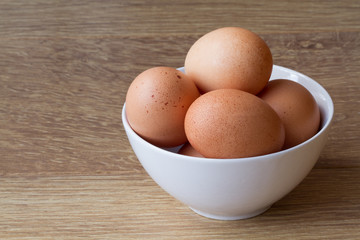 A white bowl full of fresh, brown, speckled eggs on a wooden table.