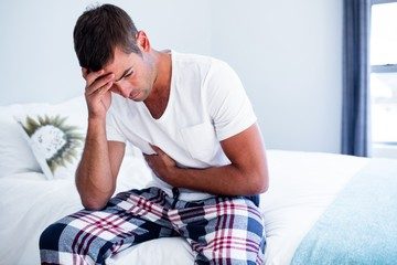 Young man sitting with stomach pain on bed