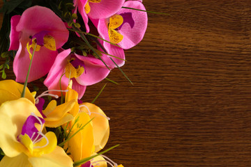 Artificial orchid on a wooden background