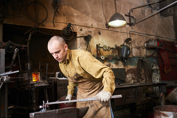 The wizard removes the excess weld using a power saw with a metal layout of a construction crane