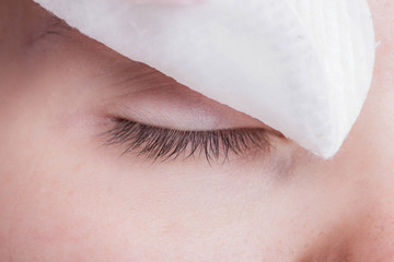 Beautiful young woman eyelash extension. Eyes close up