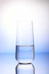 Half-filled drinking glass in drops of water