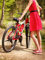 Bikes cycling girl. Girl wearing red polka dots dress rides bicycle into park. Girl in ecotourism. Cycling is good for health. Cyclist is unrecognizable.