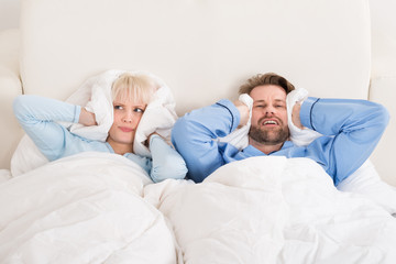 Couple Covering Ears While Sleeping On Bed