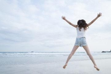 Women have to jump with open arms at the beach