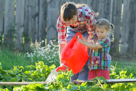 Woman gardener helping her daughter to pour vegetable garden bed with cucumbers