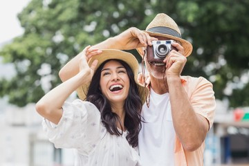 Woman looking away while man photographing