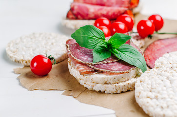 rice cakes with sausage, basil and cherry tomatoes