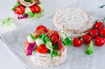 Sandwich with rice cake, lettuce, mozzarella, tomatoes and prosciutto