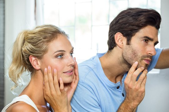 Man and woman checking their skin in bathroom