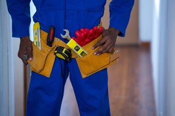Mid section of handy man wearing tool belt