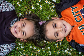 A smiling boy and a girl lying on a field with flowers