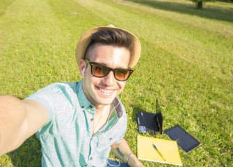 Attracive caucasian student take a selfie at the park using his smartphone