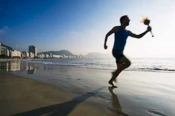 Silhouette of an athlete running with sport torch on Copacabana Beach in Rio de Janeiro, Brazil