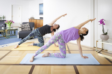 two women doing yoga at home Vasisthasana pose