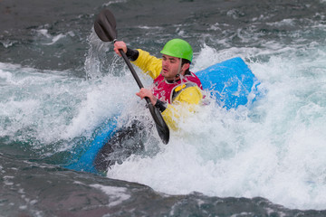 Young male man paddling a kayak in white water.  The man is holding the paddle up out of the water preparing to do a roll.