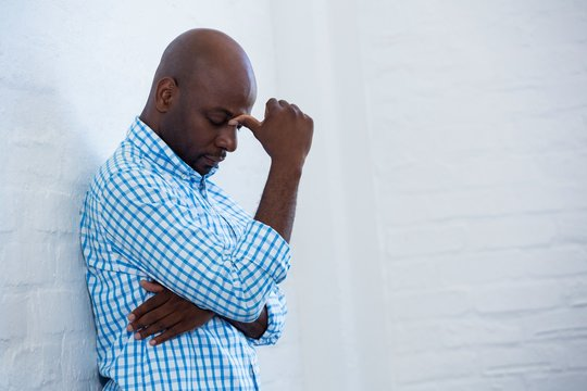 Upset man with eyes closed leaning against a wall