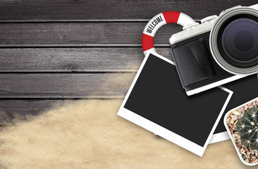 camera and blank photo frames on black wooden table. top view, travel concept