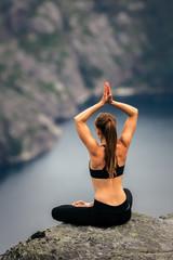 Posture de méditation de yoga sur une falaise. Lysefjord - Norvège