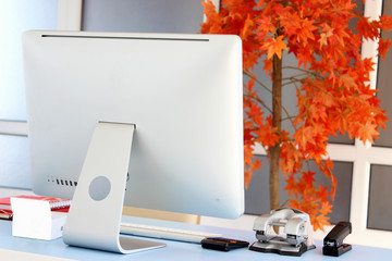 Office desk with a computer and an orange tree in the background