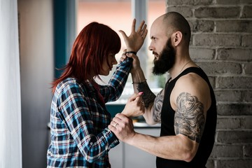 Tattooed muscular man beating his redheaded wife.
