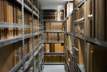 Indoor storage room details in a manufacturing enterprise, metal shelves with wooden brown office cases with folders.