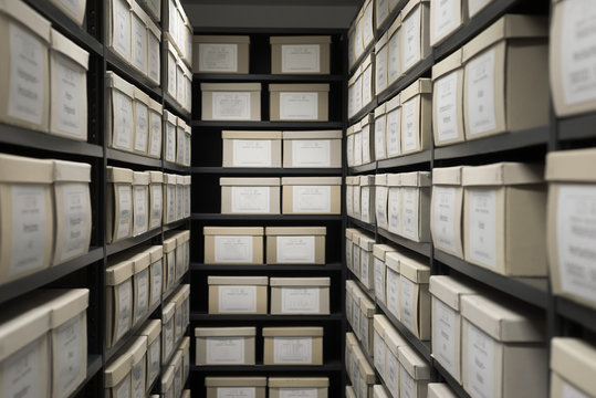 Indoor storage details in a manufacturing enterprise, black shelves with white office boxes.