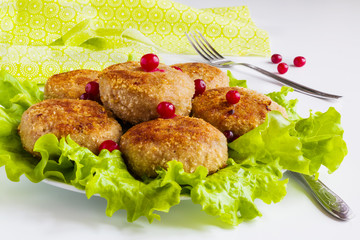 Roasted chicken cutlets on green lettuce on white table.