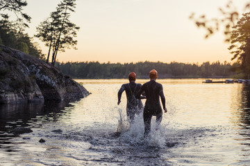 People running in water at sunset
