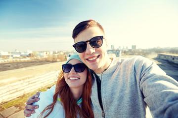 happy teenage couple taking selfie on city street