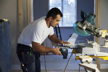 Mid-adult man cutting plank