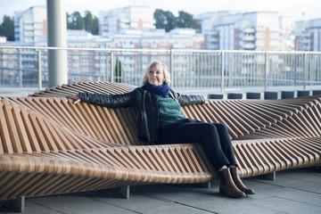 Woman sitting on modern bench