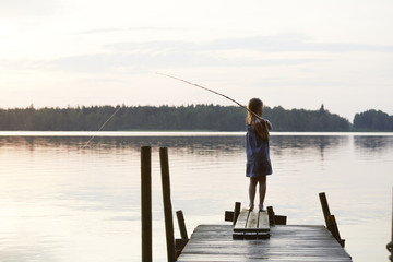 Rear view of girl fishing while standing on jetty
