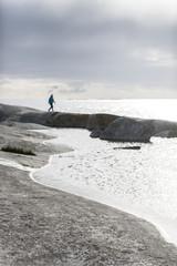 Person walking on rocky coast