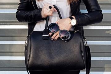 Wall Mural - Fashionable woman with black handbag . Street style