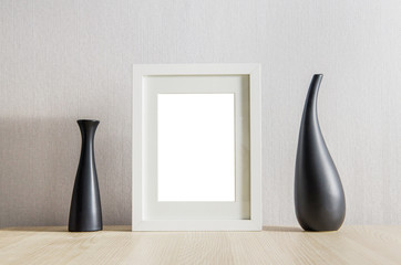 Picture frame with vase on wooden table.