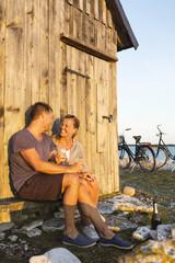 Couple near wooden house at coast