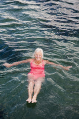 Senior woman swimming in water