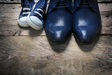 father's shoes and kids sneakers side by side on rustic wood, father's day