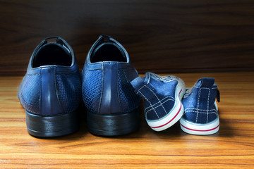 Men shoes and children sneakers side by side on the wooden floor, father's day
