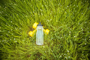 dumbbells fitness and bottle of water on a background of green grass. healthy lifestyle concept