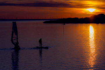 Surfing Sunset. silhouettes of surfers on the water.