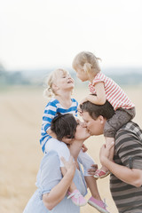 Family with two children kissing in field