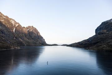 Man paddleboarding on lake